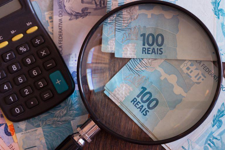 Uma calculadora e algumas notas de 100 reais vistas em uma lupa