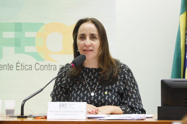 Deputada Adriana Ventura está sentada falando ao microfone