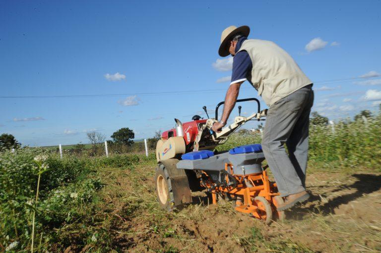 Agricultor de costas opera pequena máquina