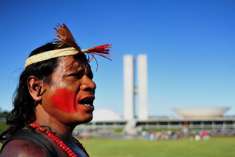 Um índio está de perfil. Ao fundo aparece o prédio do Congresso Nacional