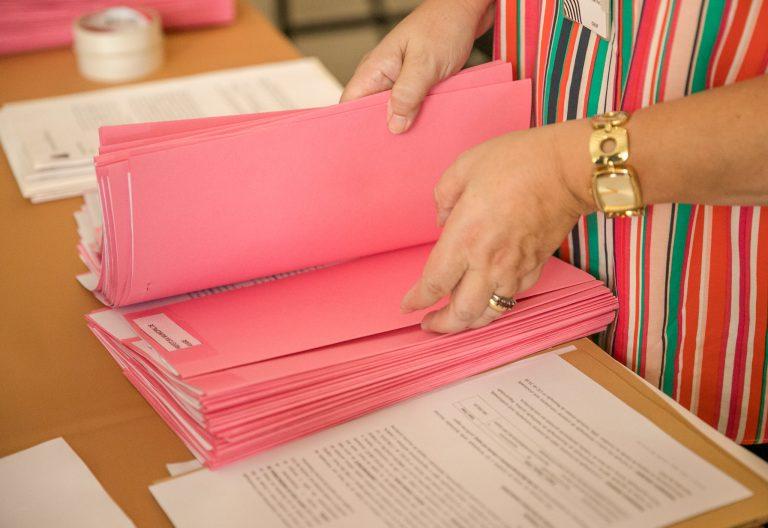 Uma mulher manuseia vários processos que estão em cima de uma mesa