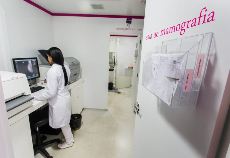 Profissional olha imagem em tela em sala de mamografia