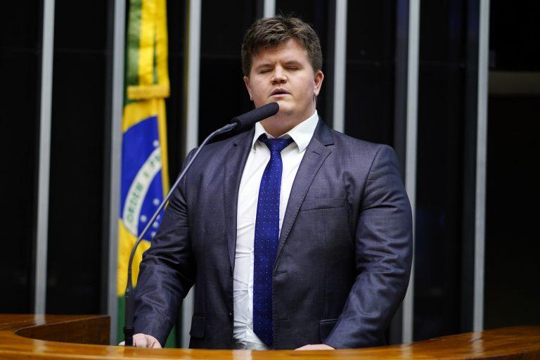Deputado Felipe Rigoni discursa no Plenário da Câmara. Ele está em pé e ao fundo há uma bandeira do Brasil