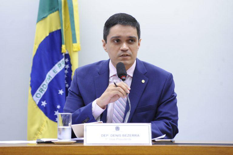 Deputado Denis Bezerra está sentado à mesa falando ao microfone