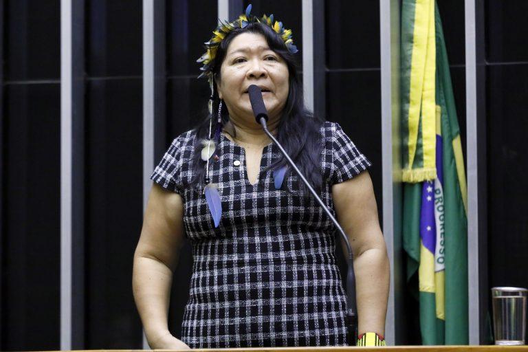 Deputada Joenia Wapichana discursa no Plenário da Câmara. Ela está em pé e usa um enfeite indígena na cabeça