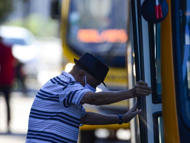 Idoso de máscara entrando em um ônibus
