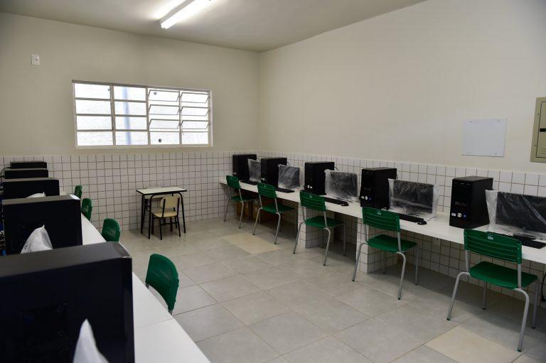 Laboratório de informática com vários computadores em cima da bancada. Não há alunos na sala