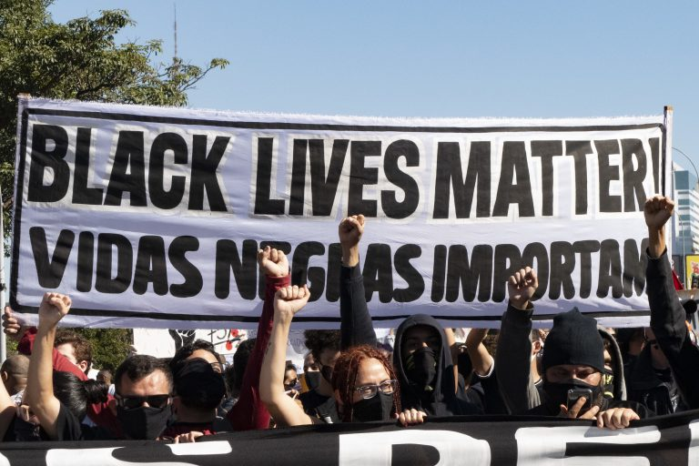 Pessoas protestam contra o racismo. Elas seguram uma faixa onde se lê: vidas negras importam