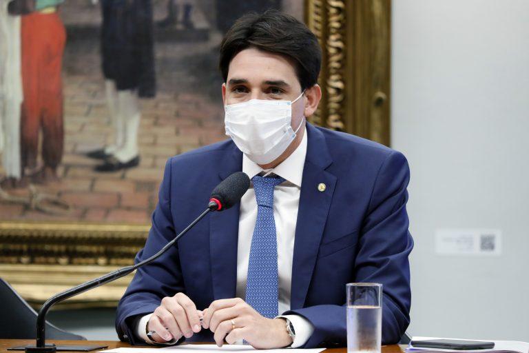 Deputado Silvio Costa Filho está sentado, de máscara, falando ao microfone