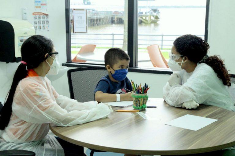 Criança com autismo e duas profissionais de saúde, todos com máscaras, em torno de uma mesa redonda