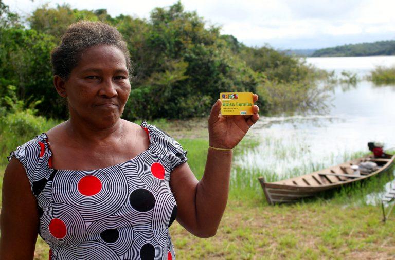 Mulher na beirra do rio, com barco ao fundo, segura cartão do Bolsa Família. Projeto de Assentamento Agroextrativista (PAE) Sapucuá Trombetas, Oriximiná-PA