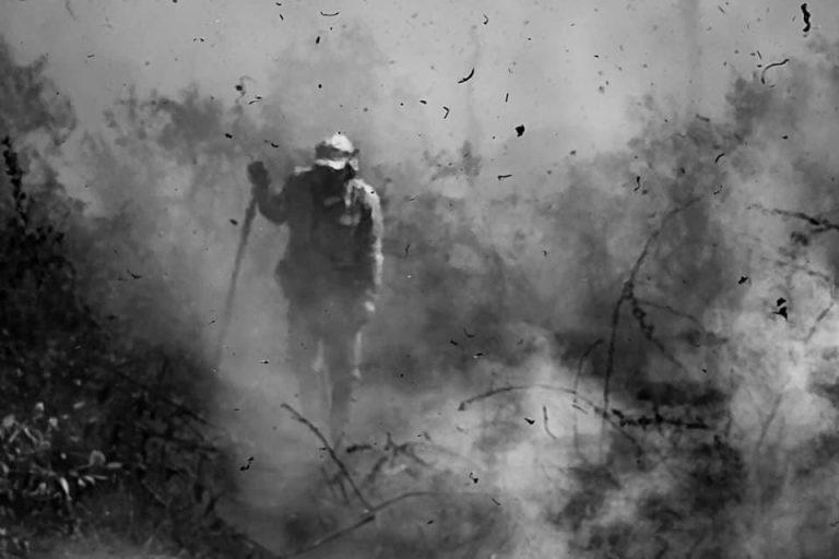 Foto em preto e branco mostra homem em roupa protegida em meio a incêndio no pantal