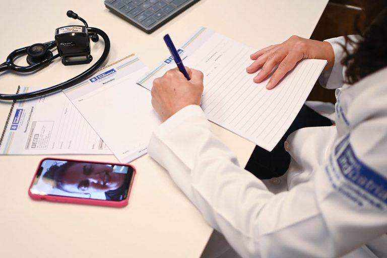 Médica faz uma teleconsulta. Ela escreve num papel enquanto fala com o paciente por chamada de vídeo no celular.