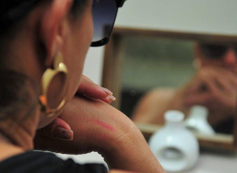 Imagem desfocada de uma mulher de óculos escuros se olhando no espelho