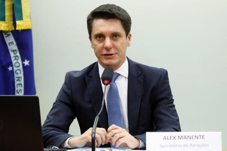 Deputado Alex Manente está sentado à mesa falando ao microfone. Ao fundo há uma bandeira do Brasil