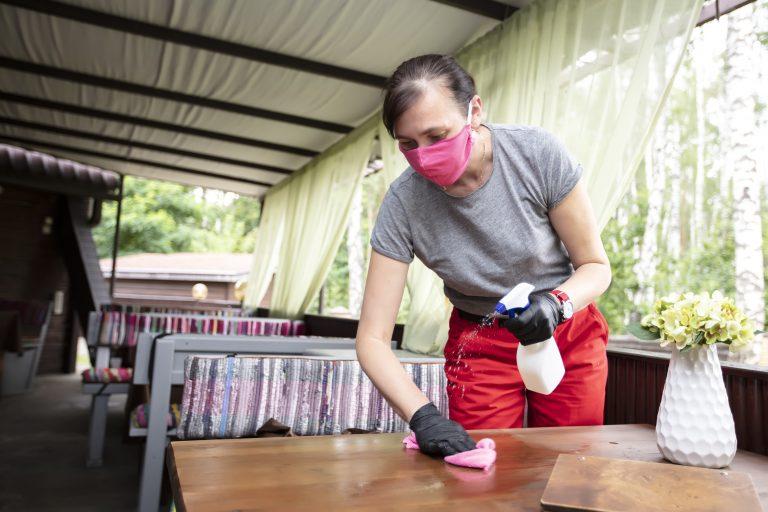 Funcionária de restaurante está com máscara de proteção facial de limpa a mesa