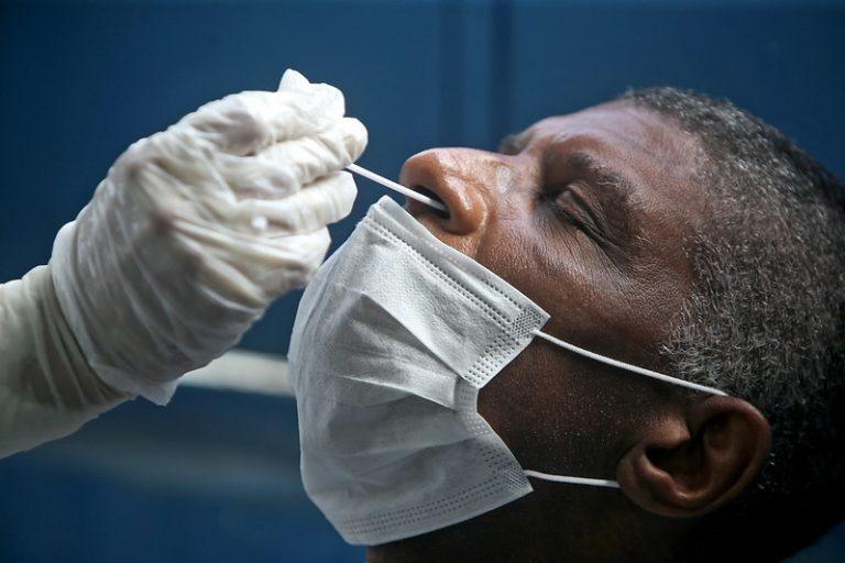 Homem negro está sentado com máscara. Uma pessoa com luva colhe material do nariz dele para detectar o novo coronavírus