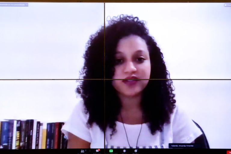 Pesquisadora Amanda Pimentel participa de videoconferência. Ela está sentada e fala olhando para o computador