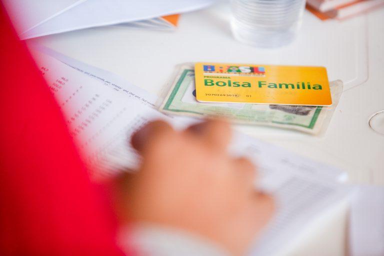 Pessoa confere uma lista com nomes. Em cima da mesa há uma carteira de identidade e um cartão do Bolsa Família