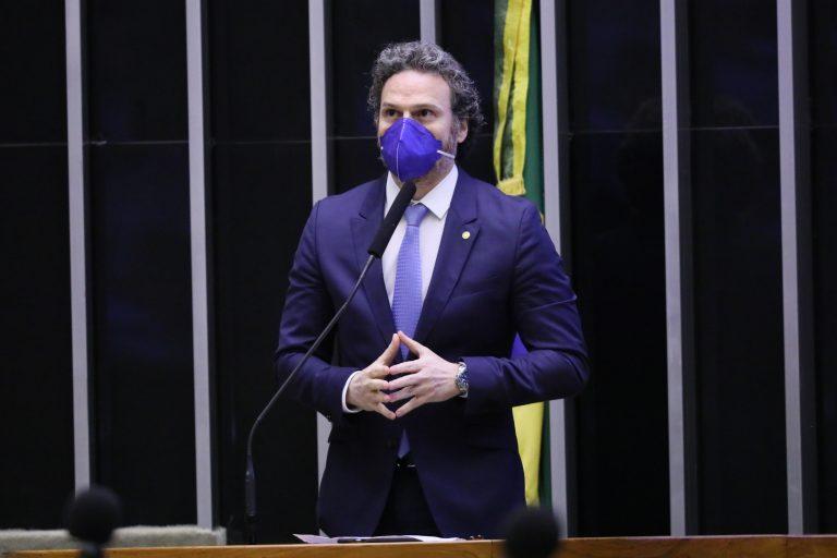 Deputado Fred Costa discursa no Plenário da Câmara. Ele está em pé e usa máscara de proteção facial