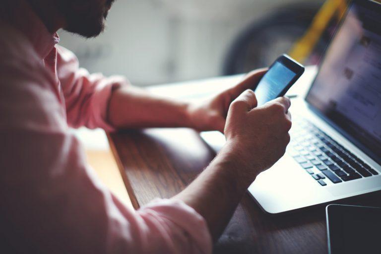 Um homem mexe no celular, ao fundo há um laptop em cima da mesa