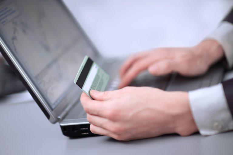Uma pessoa segura um cartão de crédito enquanto digita no computador