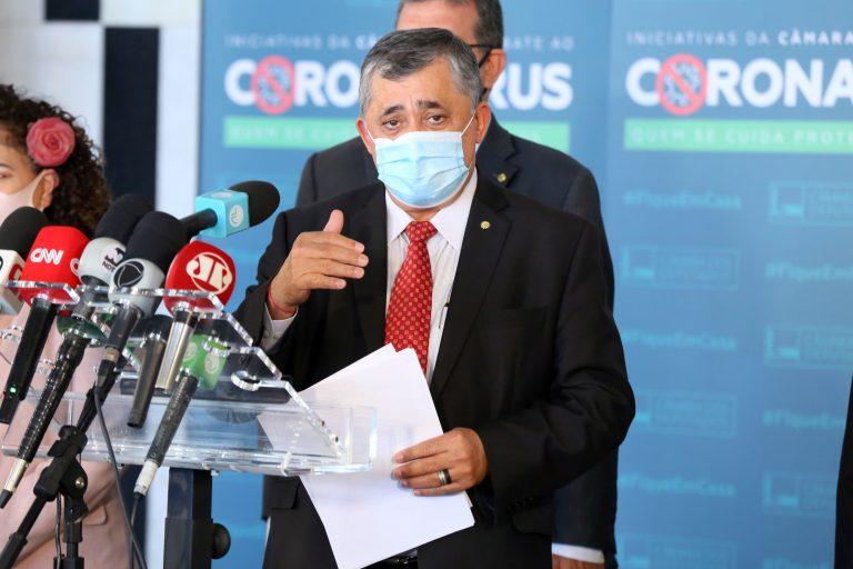 Deputado José Guimarães concede entrevista coletiva. Ele usa máscara de proteção facial e há vários microfones à frente dele