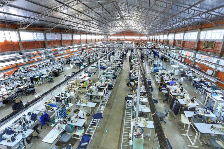 Galpão com trabalhadores em máquinas de costura industriais