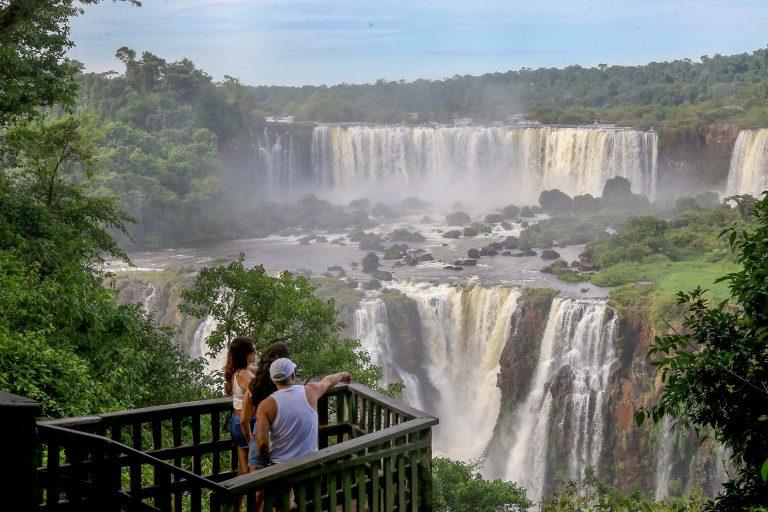 Turistas visitam as Cataratas do Iguaçu. Eles estão em uma plataforma vendo as cachoeiras