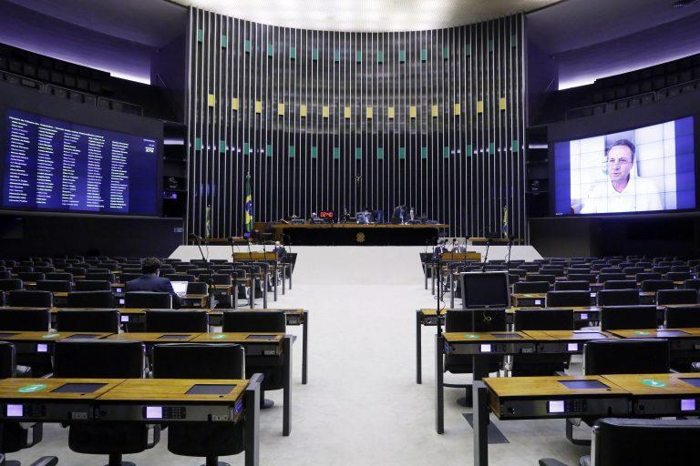 Plenário da Câmara dos Deputados vazio. Ao fundo o presidente da sessão remota e um deputado no telão