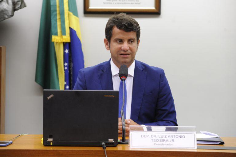 Deputado. Dr. Luiz Antonio Teixeira Jr. preside debate sobre o covid-19. Ele está sentado e fala ao microfone