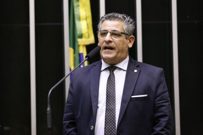 Deputado Nereu Crispim discursa no Plenário da Câmara. Ele está em pé ao microfone e ao fundo há uma bandeira do Brasil