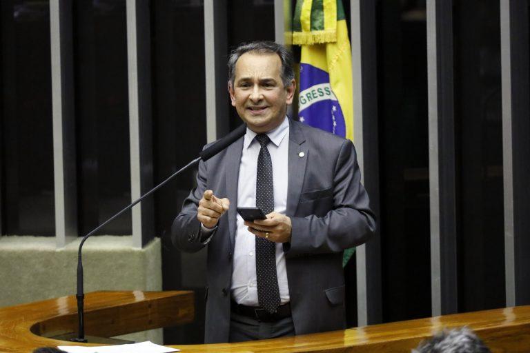 Dr. Jaziel está em pé falando ao microfone no Plenário da Câmara, atrás dele há uma bandeira do Brasil