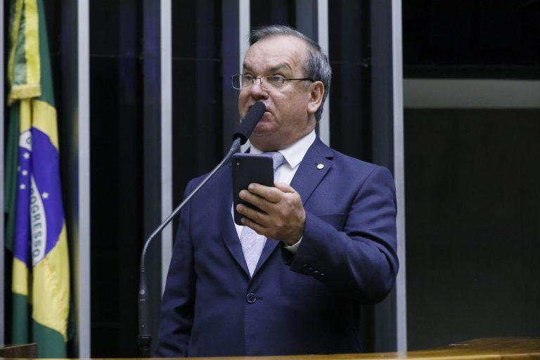 Deputado Rogério Peninha Mendonça está em pé falando ao microfone no Plenário, ao lado dele há uma bandeira do Brasil