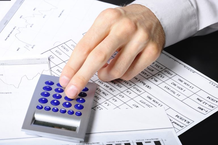 Pessoa usa calculadora sobre papeis com números