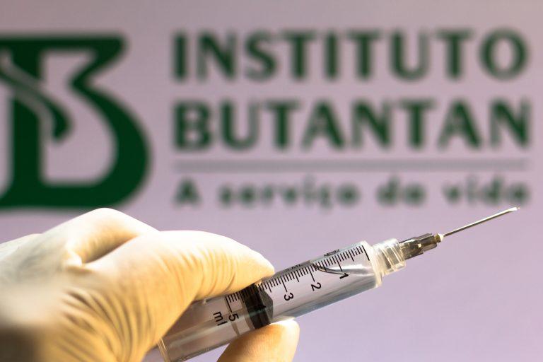 Saúde - Coronavirus - vacina - coronavac- pandemia - instituto butantan - pessoa segura seringa com placa do butantan ao fundo
