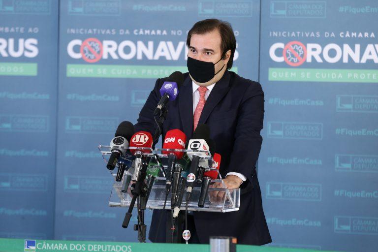 Rodrigo Maia concede entrevista coletiva. Ele está em pé e há vários microfones na mesa a sua frente