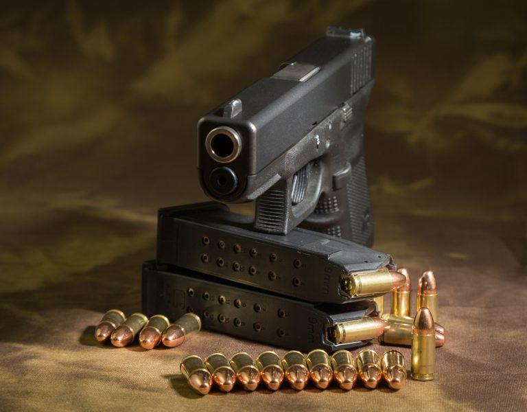 Em cima de uma mesa há uma pistola e diversas munições