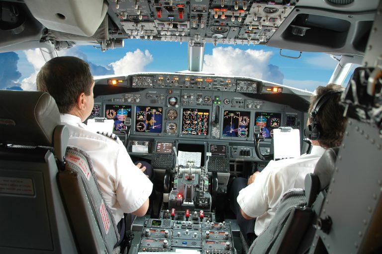 Dois pilotos estão sentados na cabine de comando de uma aeronave. À frente há um painel com muitos botões