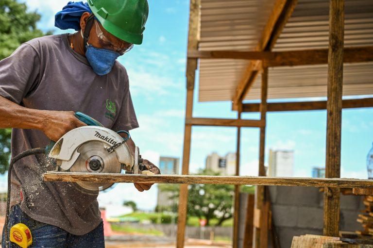 Operário corta madeira num pátio de construção