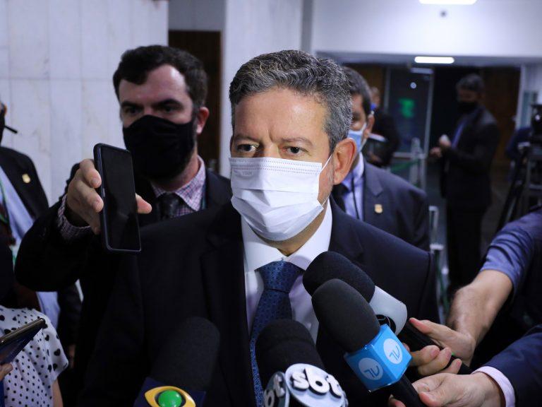 Deputado. Arthur Lira concede entrevista. Ele usa máscara facial e está cercado de microfones