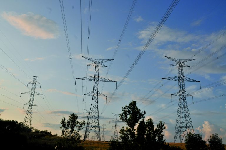 Torres de transmissão de energia elétrica estão no meio de um descampado