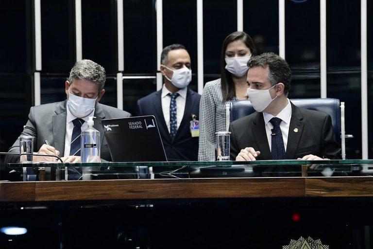 Presidente da Câmara, Arthur Lira, está sentado à mesa e assina um documento. Ao seu lado está o presidente do Senado, Rodrigo Pacheco