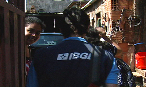 Funcionário do IBGE entrevista uma mulher no portão de casa