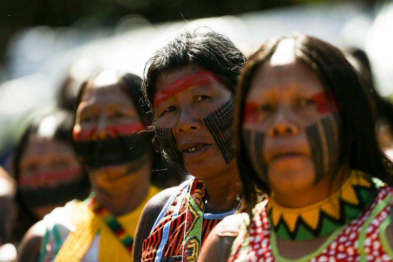 Índios com o rosto pintado olham para a câmera
