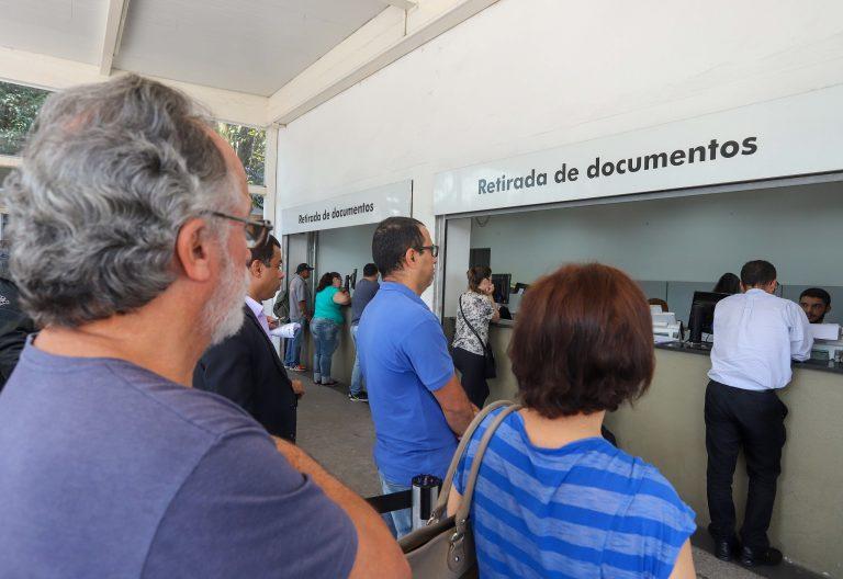 Pessoas em fila para retirada de documentos em órgão público