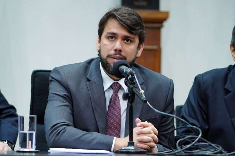 Deputado Pedro Lucas Fernandes está sentado falando ao microfone