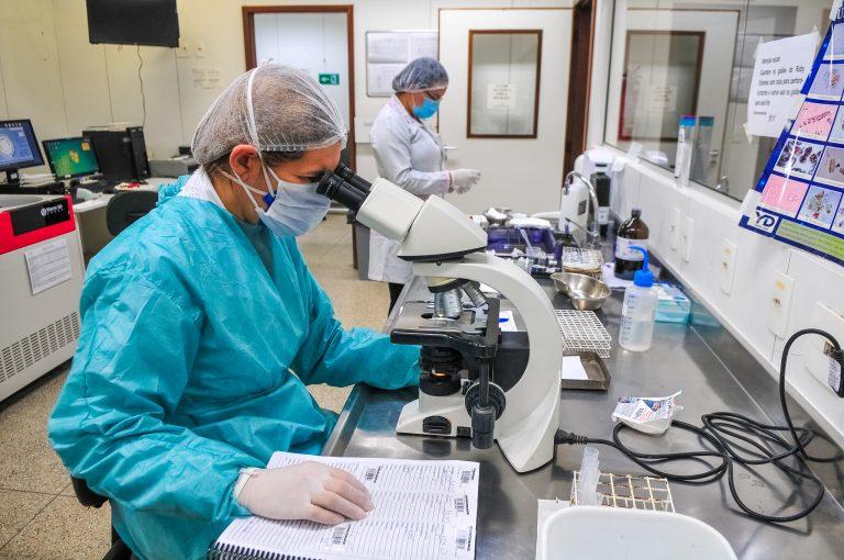 Mulher examina material em microscópio