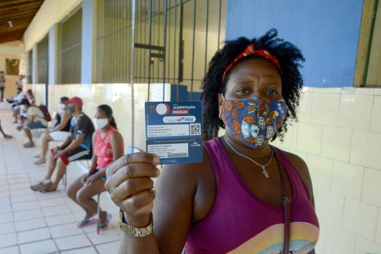 Mulher com máscara facial segura um cartão de auxílio alimentação