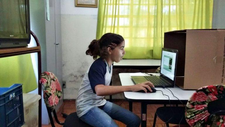 Menina usa notebook em casa